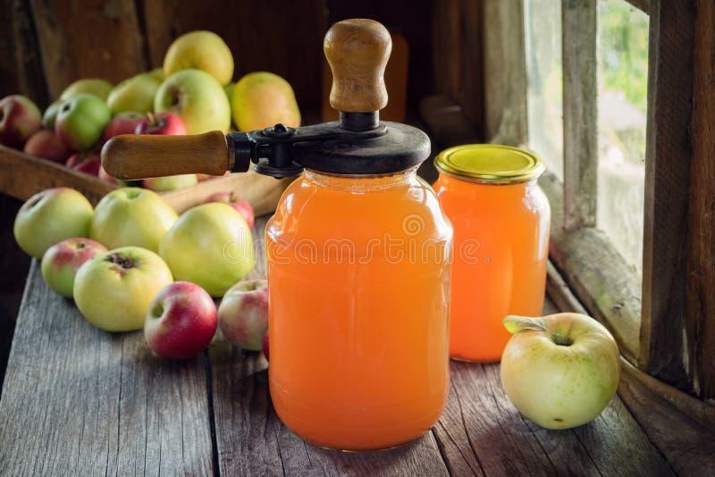 Τα βάζα του φρέσκου χυμού μήλων, φρούτα μήλων και μπορούν κλείνοντας μηχανή καπακιών για στοκ εικόνα