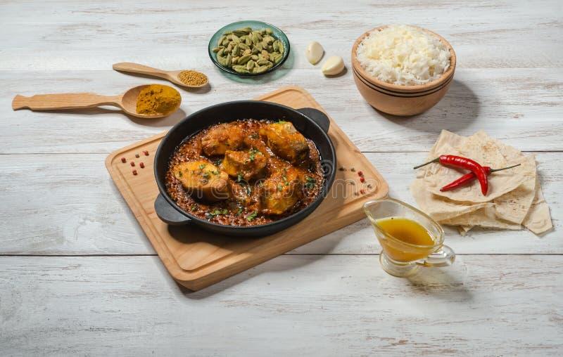 Τα βεγγαλικά ψάρια ξυστρίζουν και τα ινδικά καρυκεύματα συνόλου με basmati το ρύζι στον ξύλινο πίνακα στοκ εικόνα