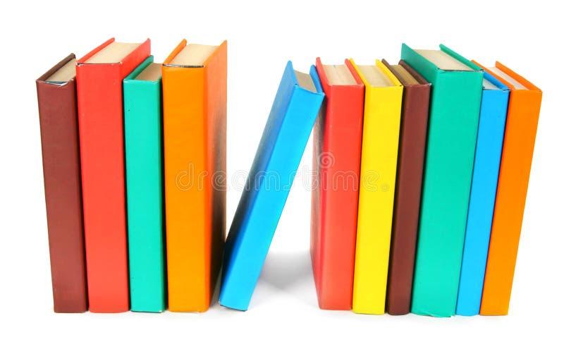 τα βιβλία χρωμάτισαν πολυ Στην άσπρη ανασκόπηση στοκ εικόνες