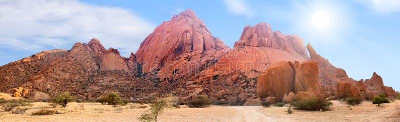 Τα βουνά Spitzkoppe κυμαίνονται την πανοραμική άποψη σχετικά με το μπλε ουρανό, τα σύννεφα και το φωτεινό υπόβαθρο ήλιων, τοπίο π στοκ φωτογραφία με δικαίωμα ελεύθερης χρήσης