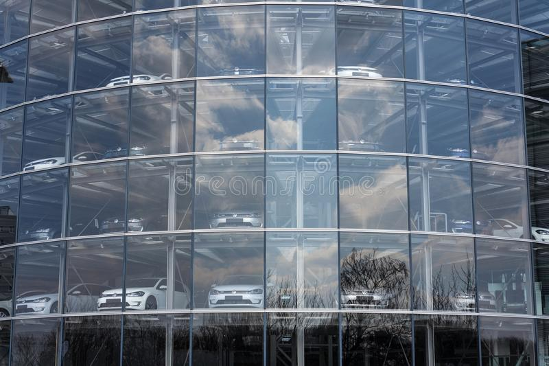 Τα βυσματωτά υβριδικά ηλεκτρικά αυτοκίνητα ε-γκολφ του Volkswagen στέκονται πίσω από το γυαλί στο Glaserne Manufaktur - διαφανές  στοκ φωτογραφία