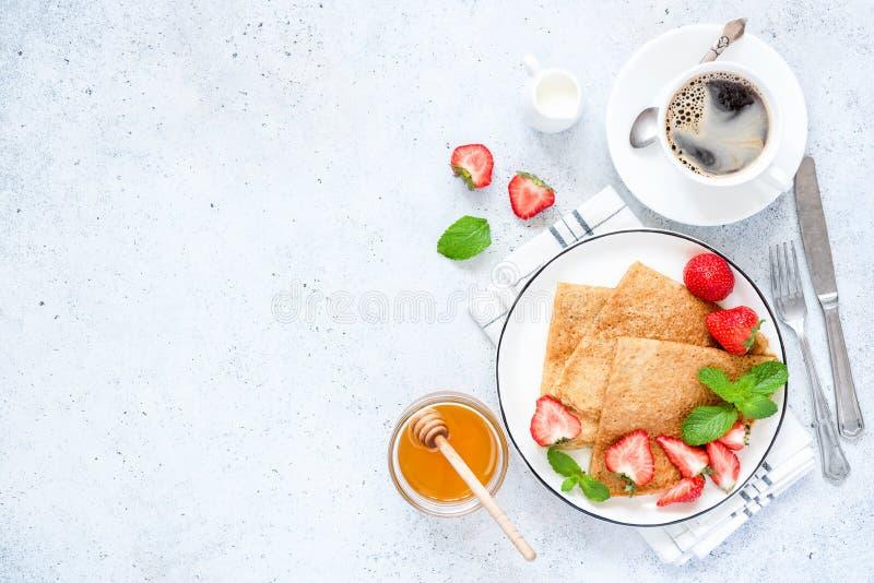Τα γαλλικά Crepes ή ρωσικό Blini με τις φρέσκες φράουλες, μέλι, καφές στοκ εικόνες