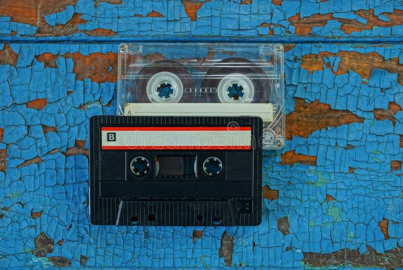 Τα γκρίζα και μαύρα παλαιά audiotapes είναι στον μπλε πίνακα στοκ φωτογραφία με δικαίωμα ελεύθερης χρήσης