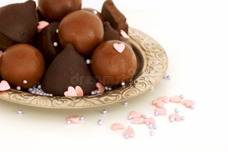 Τα γλυκά σοκολάτας συσσωρεύονται σε ένα ασημένιο πιατάκι Οι ρόδινες καρδιές βιομηχανιών ζαχαρωδών προϊόντων ψεκάζονται στοκ φωτογραφία
