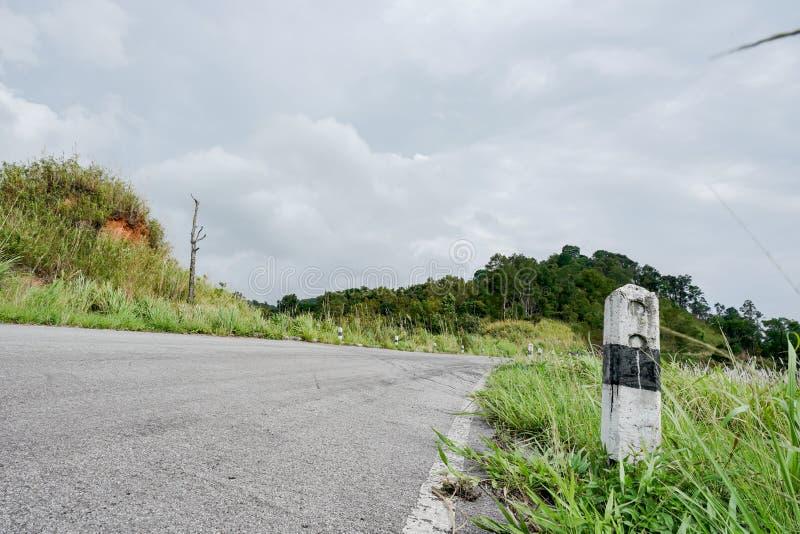 Τα γραπτά χιλιόμετρα στυλοβατών πετρών συγκεκριμένα στο δρόμο καλύπτονται με τη χλόη Με έναν γκρίζο ουρανό, δύσκολα χιλιόμετρα στοκ εικόνα