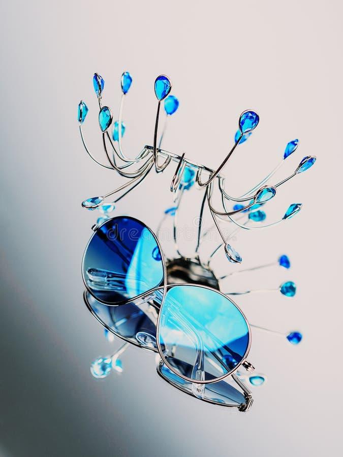 Τα γυαλιά ηλίου με τα μπλε γυαλιά σε μια σύνθεση με ένα μέταλλο στέκονται στον καθρέφτη στοκ εικόνες με δικαίωμα ελεύθερης χρήσης
