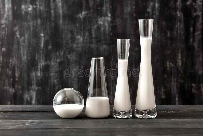 Τα γυαλιά με το γαλακτοκομικό προϊόν αρμέγουν τη στάση σε έναν μαύρο ξύλινο πίνακα στο Μαύρο Φυσικό οργανικό γαλακτοκομικό προϊόν στοκ εικόνα