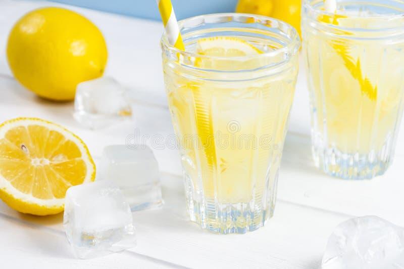 Τα γυαλιά με το καλοκαίρι πίνουν τη λεμονάδα, κύβοι φρούτων λεμονιών και πάγου στον άσπρο ξύλινο πίνακα στοκ φωτογραφία
