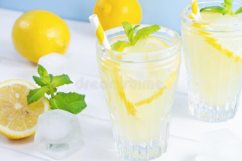 Τα γυαλιά με το καλοκαίρι πίνουν τη λεμονάδα, φύλλα φρούτων λεμονιών και μεντών στον άσπρο ξύλινο πίνακα στοκ εικόνες