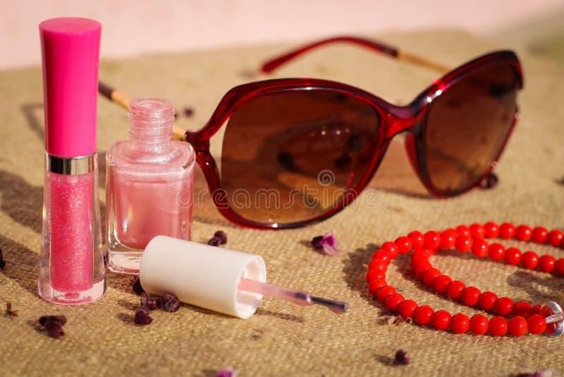 Τα γυαλιά ηλίου εξαρτημάτων των γυναικών, χείλι σχολιάζουν, καρφώνουν τη στιλβωτική ουσία, χάντρες στοκ εικόνα
