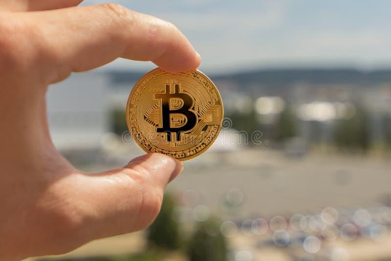 Τα δάχτυλα ατόμων κρατούν ένα μεγάλο στρογγυλό χρυσό νόμισμα bitcoin μπροστά από τη βιομηχανική πόλη στοκ φωτογραφία