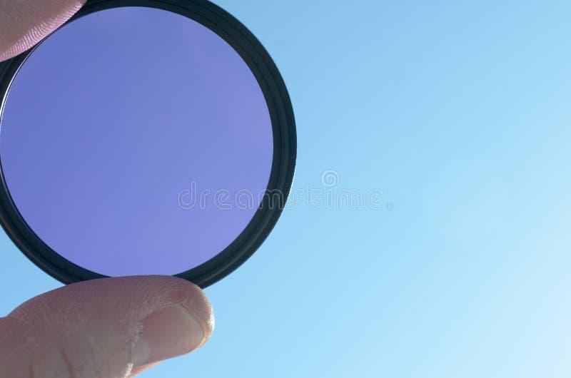 Τα δάχτυλα κρατούν το φίλτρο φωτογραφιών ενάντια στο μπλε ουρανό στοκ εικόνα