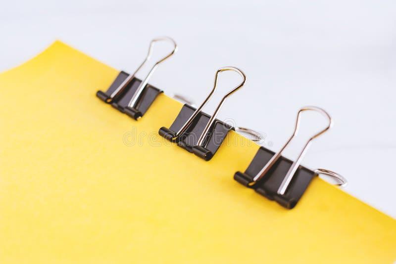 Τα δεσμευτικά φύλλα συνδετήρων συνδέσμων του κίτρινου εγγράφου μαζί για το λευκό χαλούν στοκ φωτογραφία