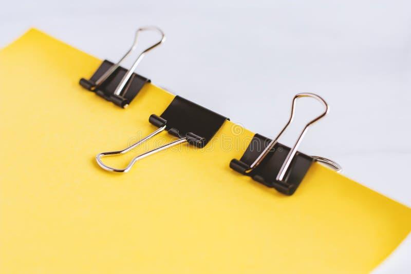 Τα δεσμευτικά φύλλα συνδετήρων συνδέσμων του κίτρινου εγγράφου μαζί για το λευκό χαλούν στοκ φωτογραφίες