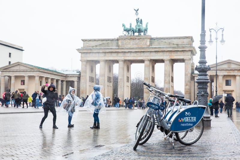 Τα δημόσιοι ποδήλατα και οι τουρίστες στην πύλη του Βραδεμβούργου είδαν από το Pariser Platz στη ανατολική πλευρά σε ένα χιονώδες στοκ φωτογραφία