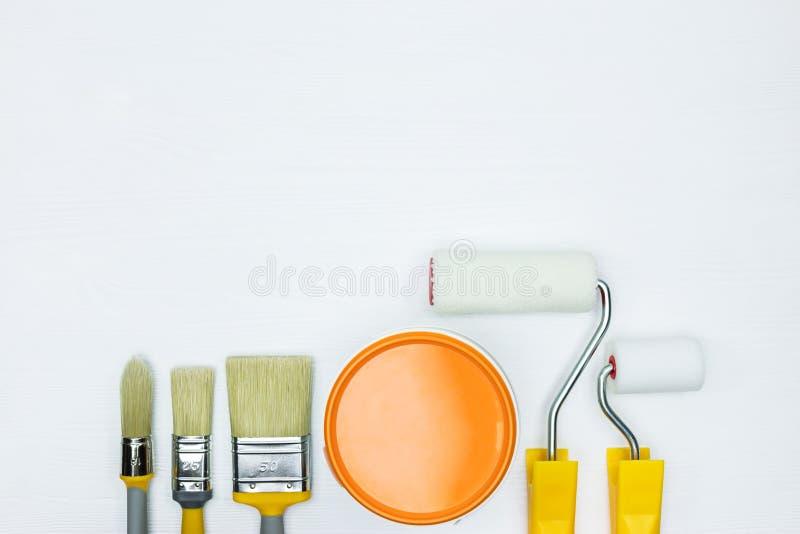 Τα διάφοροι πινέλα και οι κύλινδροι, μπορούν πορτοκαλιού να χρωματίσουν στο άσπρο W στοκ φωτογραφία με δικαίωμα ελεύθερης χρήσης