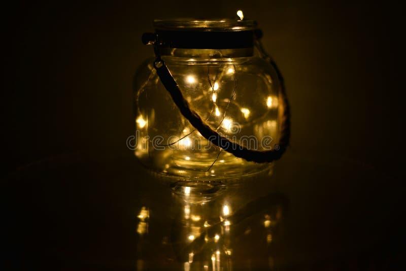 Τα διακοσμητικά φω'τα στο βάζο γυαλιού στο σκοτεινό δωμάτιο με τον καθρέφτη επηρεάζουν στο σκοτεινό υπόβαθρο διακοσμήσεις εορταστ στοκ εικόνα