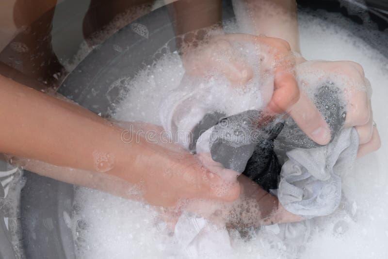 Τα διπλά ενδύματα πλυσιμάτων γυναικών έκθεσης παραδίδουν κοντά το σαπωνώδες νερό στο άσπρο υπόβαθρο στοκ φωτογραφίες