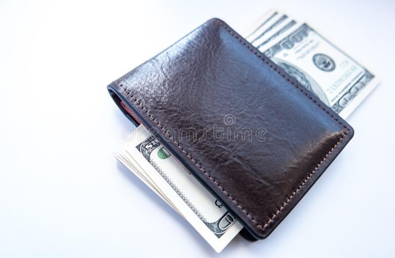 Τα δολάρια είναι στον πίνακα σε ένα καφετί πορτοφόλι στοκ φωτογραφίες