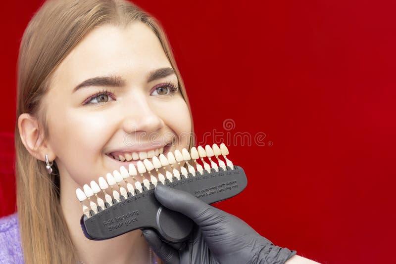 Τα δόντια που λευκαίνουν τον οδοντίατρο διαδικασίας επιλέγουν την αρχική σκιά των δοντιών του κοριτσιού στοκ εικόνες