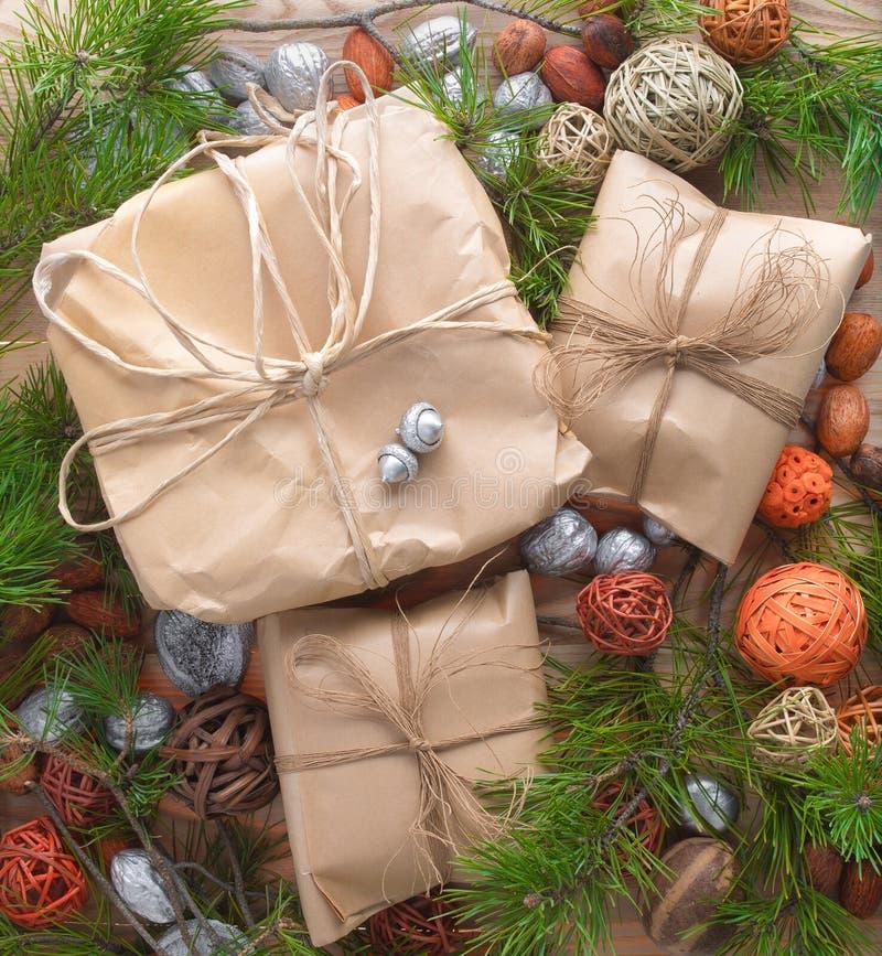 Τα δώρα Χριστουγέννων στη συσκευασία εγγράφου τεχνών έδεσαν ένα σχοινί στο ξύλινο υπόβαθρο στις διακοσμήσεις κλάδων πλαισίων χρισ στοκ φωτογραφίες με δικαίωμα ελεύθερης χρήσης