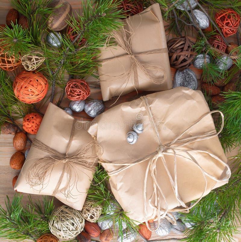 Τα δώρα Χριστουγέννων στη συσκευασία εγγράφου τεχνών έδεσαν ένα σχοινί στο ξύλινο υπόβαθρο στις διακοσμήσεις κλάδων πλαισίων χρισ στοκ εικόνα