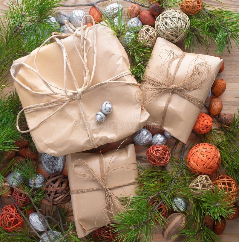 Τα δώρα Χριστουγέννων στη συσκευασία εγγράφου τεχνών έδεσαν ένα σχοινί στο ξύλινο υπόβαθρο στις διακοσμήσεις κλάδων πλαισίων χρισ στοκ φωτογραφία