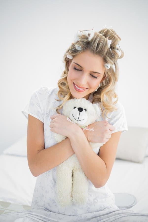 Τα ειρηνικά αρκετά ξανθά φορώντας ρόλερ τρίχας που κρατούν teddy αντέχουν στοκ εικόνα με δικαίωμα ελεύθερης χρήσης