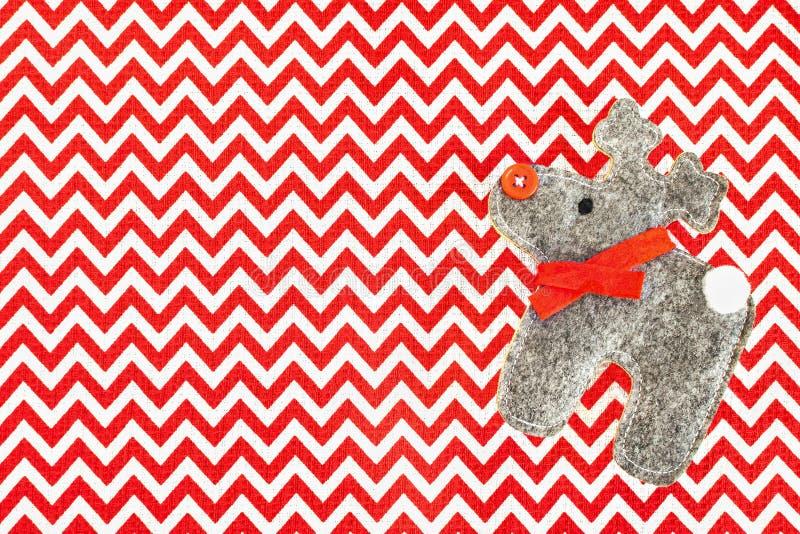 Τα ελάφια αισθάνθηκαν με την κόκκινη μύτη κουμπιών στο κόκκινο άσπρο τραπεζομάντιλο υφασμάτων, τα Χριστούγεννα ή το νέο υπόβαθρο  στοκ εικόνα με δικαίωμα ελεύθερης χρήσης