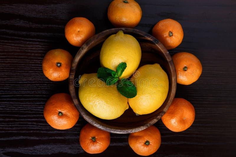 Τα λεμόνια στο ξύλινο πιάτο με τα μανταρίνια και τη μέντα βγάζουν φύλλα στη σκοτεινή μακροεντολή κινηματογραφήσεων σε πρώτο πλάνο στοκ φωτογραφίες