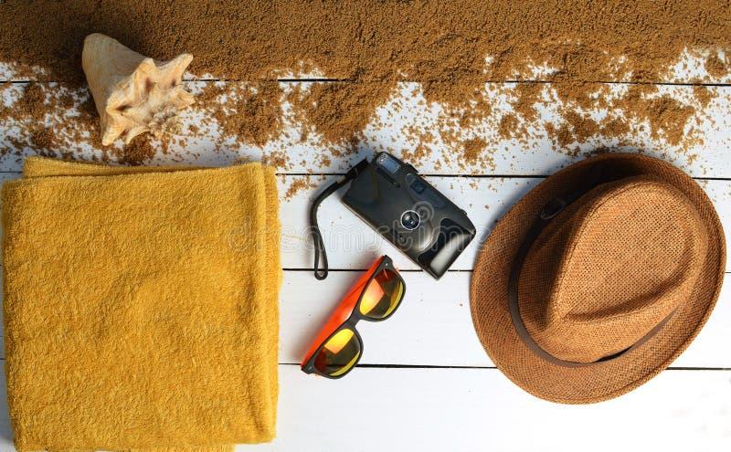 Τα εξαρτήματα παραλιών σχεδιάζονται σε μια άσπρη ξύλινη επιφάνεια Καπέλο, κάμερα, γυαλιά ηλίου, πετσέτα Η έννοια να χαλαρώσει εν  στοκ εικόνες