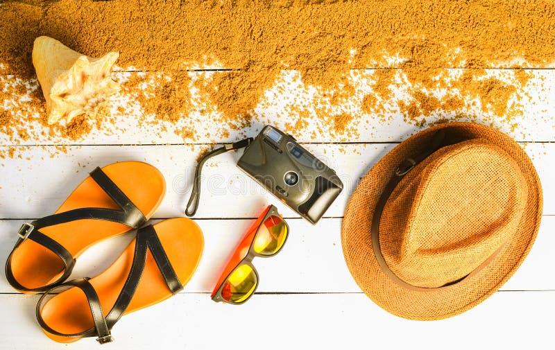 Τα εξαρτήματα παραλιών σχεδιάζονται σε μια άσπρη ξύλινη επιφάνεια Καπέλο, κάμερα, σανδάλια, γυαλιά ηλίου Η έννοια να χαλαρώσει εν στοκ φωτογραφία με δικαίωμα ελεύθερης χρήσης