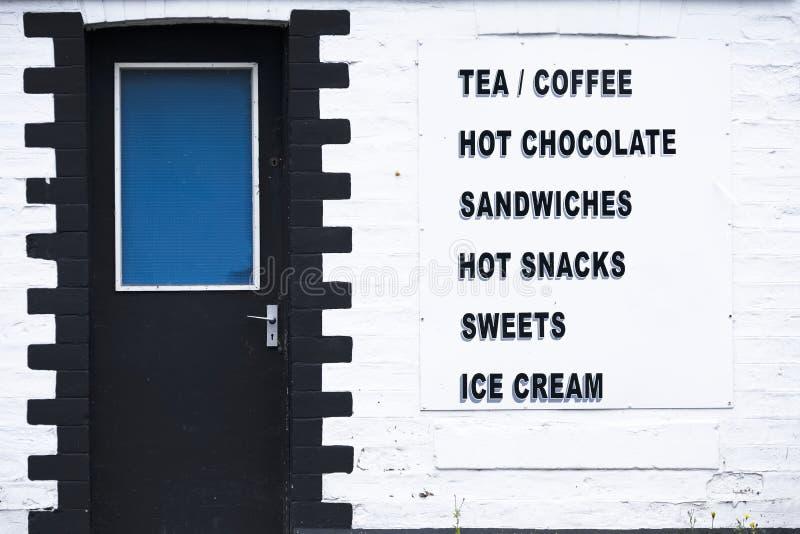 Τα εξυπηρετώντας γλυκά και το παγωτό πρόχειρων φαγητών σάντουιτς καφέδων δωματίων καφέ τσαγιού καυτά υπογράφουν στον άσπρο τοίχο στοκ φωτογραφία με δικαίωμα ελεύθερης χρήσης