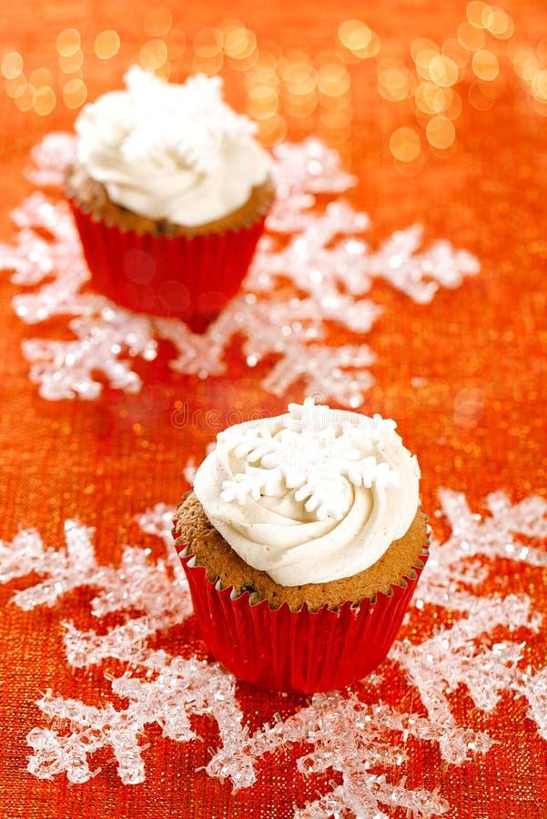 Τα εορταστικά cupcakes, snowflake, κόκκινος χρυσός ακτινοβολούν στοκ εικόνες