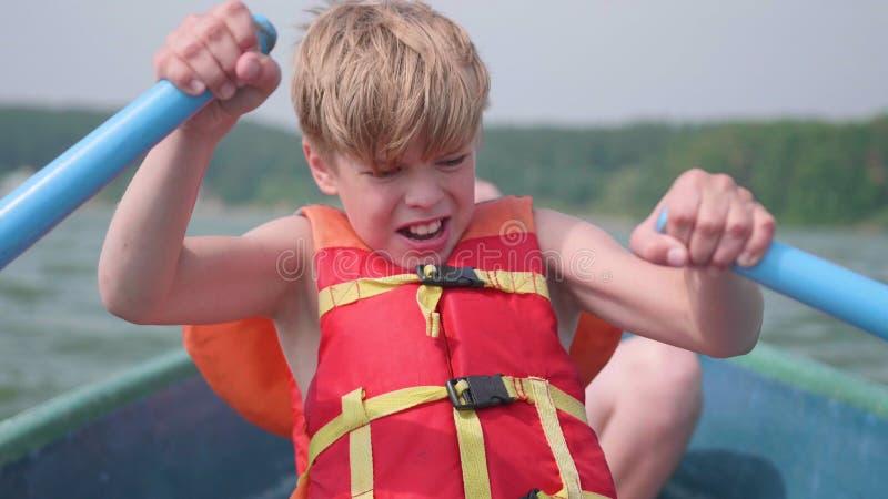 Τα επιπλέοντα σώματα τύπων στη βάρκα Ο έφηβος ενεργοποιεί ανεξάρτητα μια βάρκα με τη βοήθεια των κουπιών ακραίος αθλητισμός στοκ φωτογραφία με δικαίωμα ελεύθερης χρήσης
