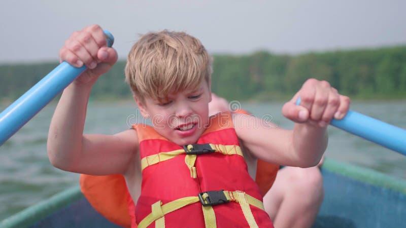 Τα επιπλέοντα σώματα τύπων στη βάρκα Ο έφηβος ενεργοποιεί ανεξάρτητα μια βάρκα με τη βοήθεια των κουπιών ακραίος αθλητισμός στοκ φωτογραφίες με δικαίωμα ελεύθερης χρήσης