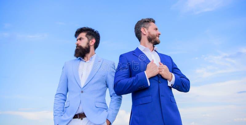Τα επιχειρησιακά άτομα στέκονται το υπόβαθρο μπλε ουρανού Έννοια επιχειρηματιών Η καλά καλλωπισμένη εμφάνιση βελτιώνει την επιχει στοκ φωτογραφίες με δικαίωμα ελεύθερης χρήσης
