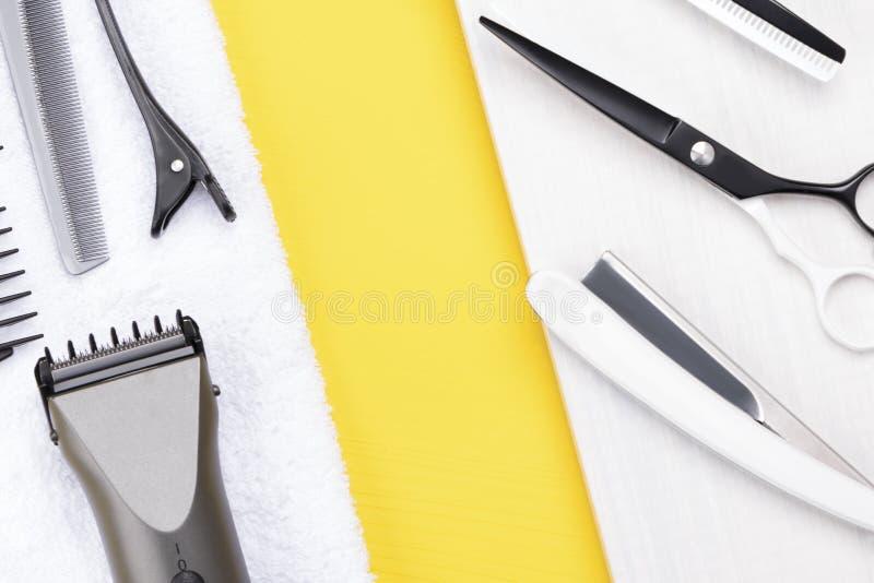 Τα εργαλεία για την κοπή τρίχας βρίσκονται σε μια άσπρη πετσέτα σε ένα κίτρινο υπόβαθρο στοκ εικόνα