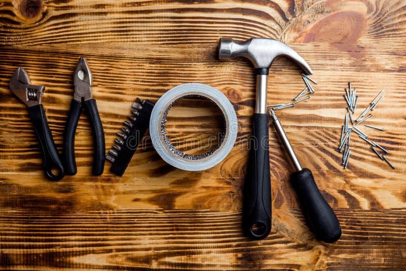 Τα εργαλεία εργασίας/οικοδόμησης στο σκοτεινό ξύλινο υπόβαθρο συνδύασαν στην εργασία ` λέξης ` Τοπ όψη στοκ φωτογραφία με δικαίωμα ελεύθερης χρήσης