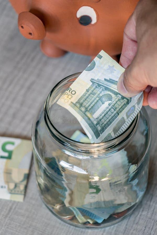 Τα ευρώ αποταμίευσης στο γυαλί μπορούν ενώ ρολόγια χοίρων τραπεζών στοκ φωτογραφία με δικαίωμα ελεύθερης χρήσης