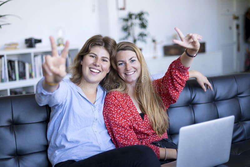 Τα ευτυχή έφηβη που κάθονται σε έναν καναπέ με ένα lap-top που κάνει τη νίκη υπογράφουν στοκ εικόνες