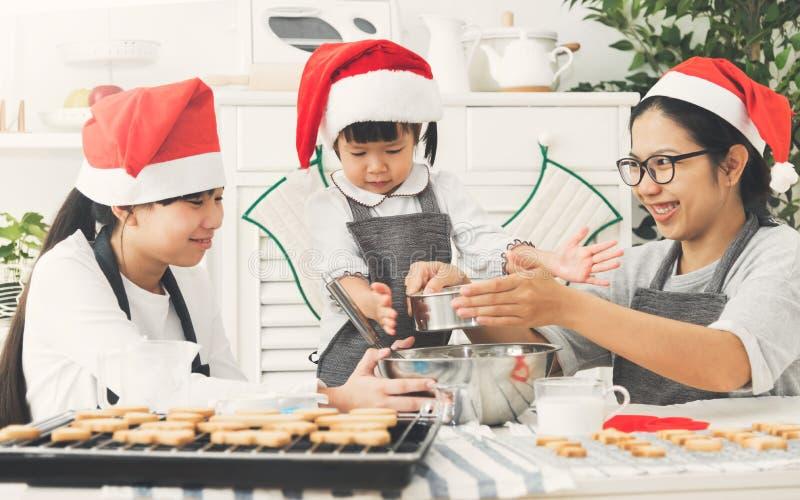 Τα ευτυχή ασιατικά καπέλα Santa οικογενειακής ένδυσης που προετοιμάζουν τη ζύμη, ψήνουν το γουργούρισμα στοκ φωτογραφία