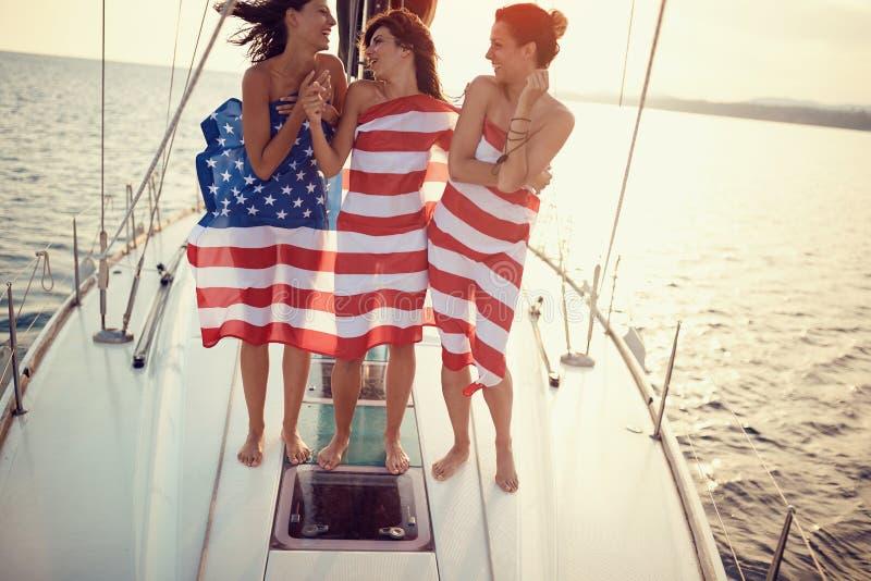 Τα ευτυχή κορίτσια στο γιοτ έχουν το κόμμα στη αμερικανική σημαία στοκ φωτογραφίες