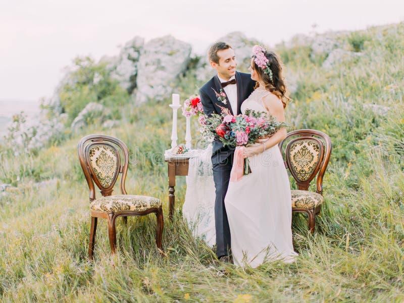 Τα ευτυχή newlyweds ξοδεύουν το χρόνο στα βουνά Η σύνθεση του συνόλου γαμήλιων πινάκων στοκ φωτογραφία