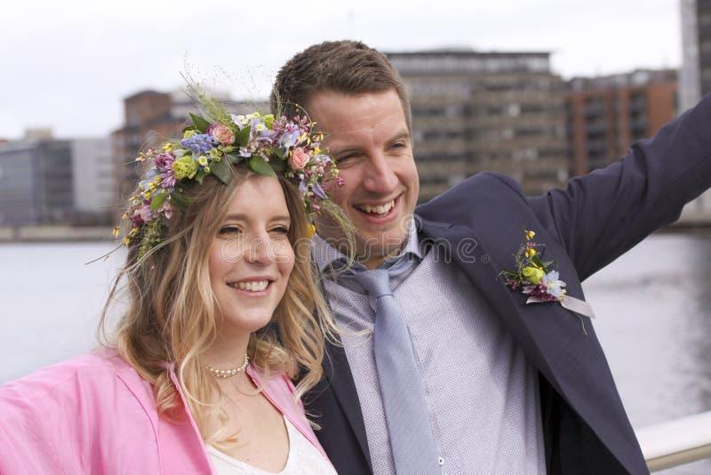 Τα ευτυχή newlyweds πάντρεψαν ακριβώς το ζεύγος γαμήλιων ζευγών που χαμογελά - όμορφο κορίτσι με την ανθοδέσμη των λουλουδιών και στοκ φωτογραφία με δικαίωμα ελεύθερης χρήσης
