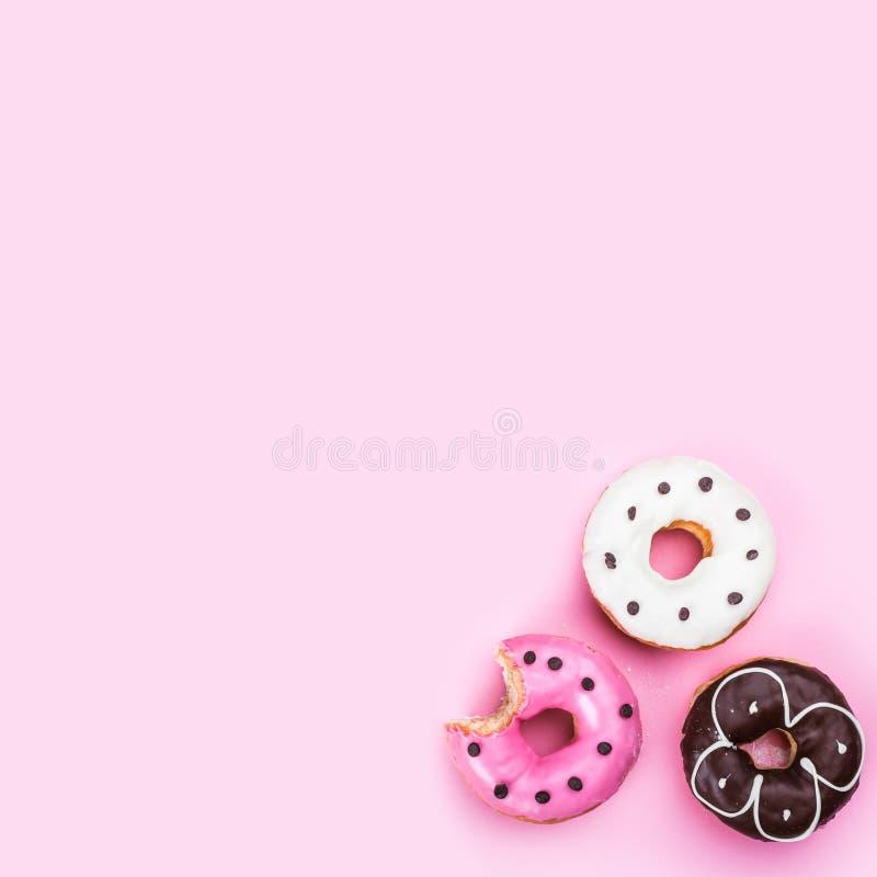 Τα εύγευστα donuts με τη σοκολάτα αποβουτυρώνουν, μαρμελάδα φραουλών, άσπρη σοκολάτα και ρόδινη καραμέλα που βερνικώνονται στοκ φωτογραφία