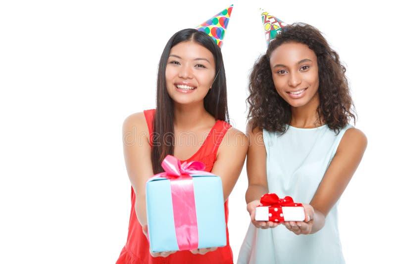 Τα εύθυμα κορίτσια που κρατούν τα γενέθλια παρουσιάζουν στοκ εικόνες