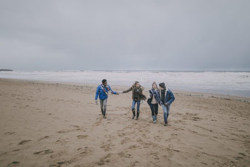 Τα ζεύγη περπατούν κατά μήκος της χειμερινής παραλίας στοκ φωτογραφίες