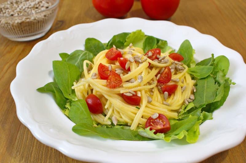 Τα ζυμαρικά με τις ντομάτες, τους σπόρους ηλίανθων και τη σαλάτα εξυπηρέτησαν στον ξύλινο πίνακα στοκ φωτογραφία με δικαίωμα ελεύθερης χρήσης