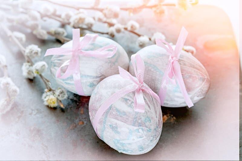 Τα ζωηρόχρωμα αυγά Πάσχας που βρίσκονται σε ένα όμορφο εκλεκτής ποιότητας υπόβαθρο με την ανθοδέσμη φιαγμένο από ιτιά διακλαδίζον στοκ εικόνες